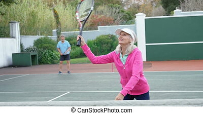 Senior woman playing tennis in tennis court 4k - Smiling...