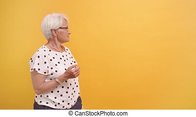 Senior woman pointing finger on empty advertisement space. Orange background. High quality 4k footage