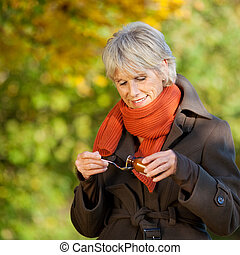 Senior Woman Pouring Syrup In Spoon - Senior woman in jacket...