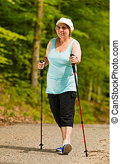 Senior woman practicing nordic walking in park