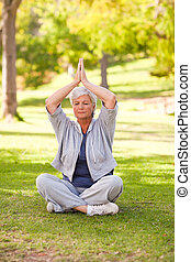 Senior woman practicing yoga in the