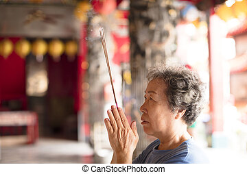 senior woman praying buddha with incense stick at temple