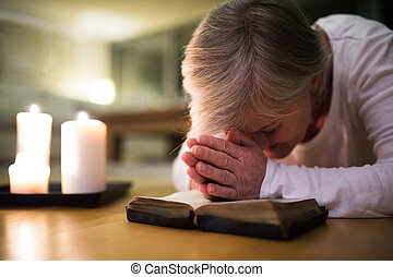 Senior woman praying, hands clasped together on her Bible.