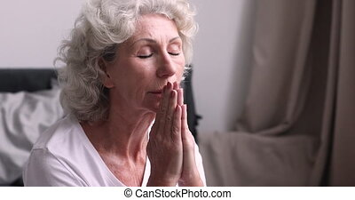 Senior woman praying with eyes closed in bedroom, close up...