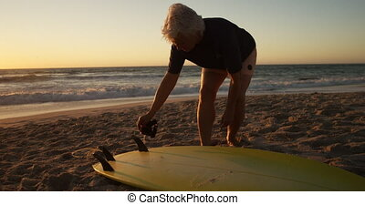 Senior woman preparing to surf at the beach - Side view of a...