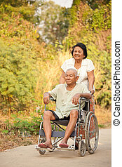 Senior woman pushing her disabled hasband on wheelchair