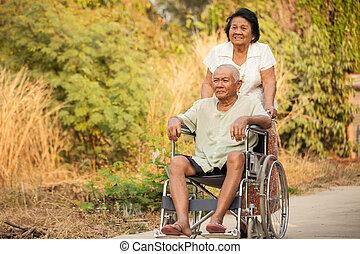 Senior woman pushing her disabled husband on wheelchair