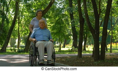 Senior woman pushing husband in wheelchair