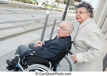 senior woman pushing husband in wheelchair to cross street