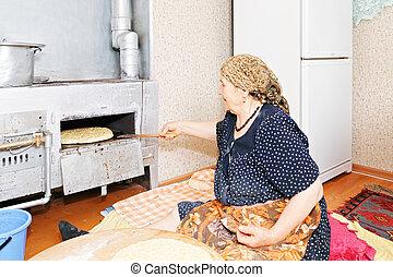 Senior woman putting bread into oven
