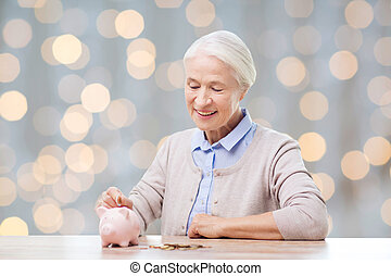 senior woman putting money to piggy bank