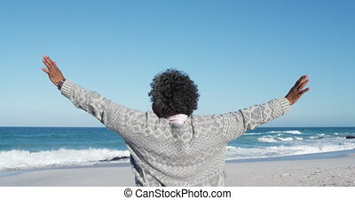 Senior woman raising her arms at the beach