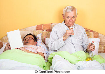 Senior woman reading and drunken man in bed