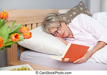 Senior Woman Reading Book While Lying In Bed