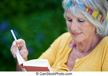 Senior Woman Reading Book While Smoking Cigarette