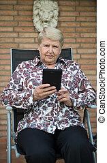 Senior woman reading e-book