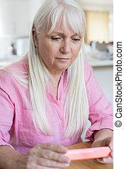 Senior Woman Reading Information On Drug Packaging