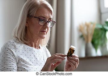 Senior woman reading medicines instruction on pills bottle