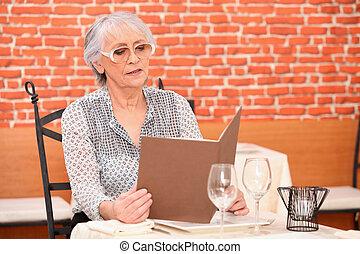 Senior woman reading menu at the restaurant