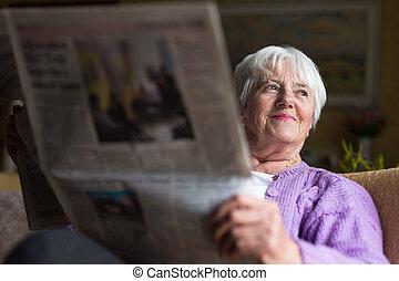 Senior woman reading morning newspaper, sitting in her ...