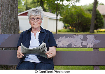 Senior Woman Reading Newspaper in Park