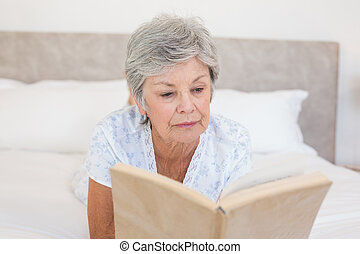 Senior woman reading story book in bed