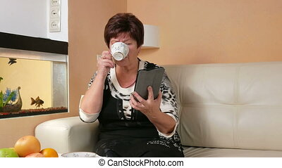 Senior woman reads the news on tablet computer and drinking coffee. She sits on the couch at home near the aquarium. holiday home concept