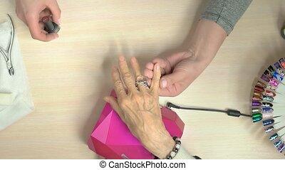 Senior woman receiving manicure in nail salon.