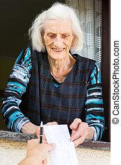 Senior woman receiving retirement check at home