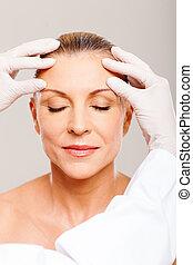 senior woman receiving skin check before surgery
