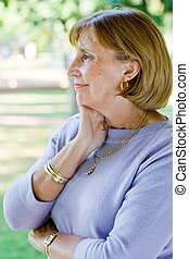senior woman reflecting - a senior woman with her hand on...