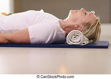Senior woman relaxing and doing therapy with crystals -...
