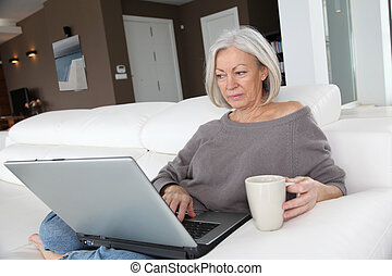 Senior woman relaxing at home in front of laptop computer