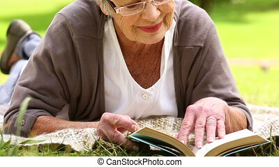 Senior woman relaxing in the park reading