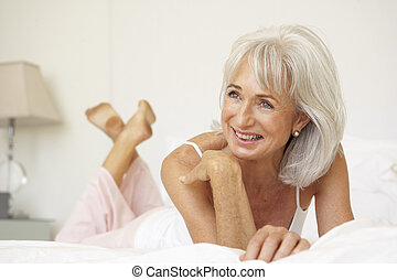 Senior Woman Relaxing On Bed