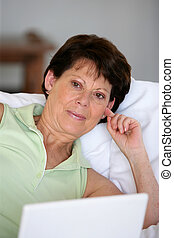 senior woman relaxing on the couch with her laptop