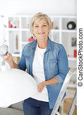 senior woman replacing light bulb at home