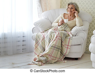 Senior woman resting at home with tea cup