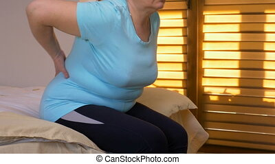 Senior woman rubbing her lower back trying to relax her pain