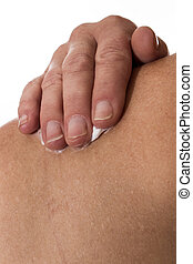 senior female rubbing her shoulder with a white pain relieving cream