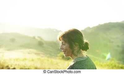 Senior woman runner walking on meadow outdoors at sunrise in...