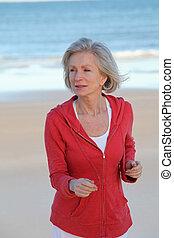 Senior woman running by the beach