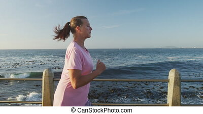 Senior Caucasian woman working out on promenade by the sea wearing sports clothes, running with smartwatch on in slow motion. Retirement healthy lifestyle activity.
