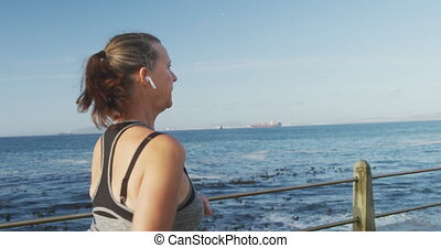 Senior Caucasian woman working out on promenade by the sea wearing sports clothes, running with earphones on in slow motion. Retirement healthy lifestyle activity.