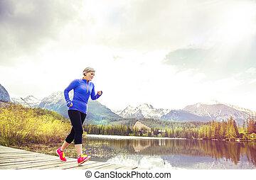 Senior woman running - Senior woman jogging round the tarn...
