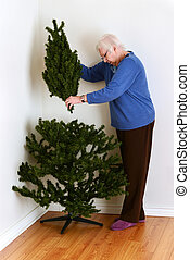 senior woman setting up tree