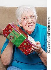 senior woman shaking present