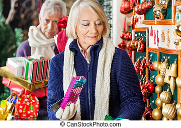 Senior Woman Shopping At Christmas Store