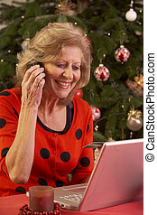 Senior Woman Shopping Online For Christmas Gifts On Phone