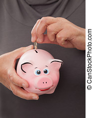 senior woman showing a piggy bank